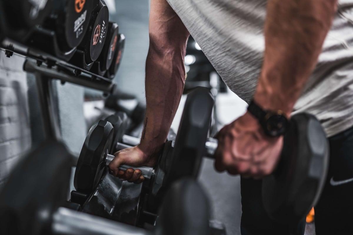 Un'atleta prende 2 manubri per allenarsi.