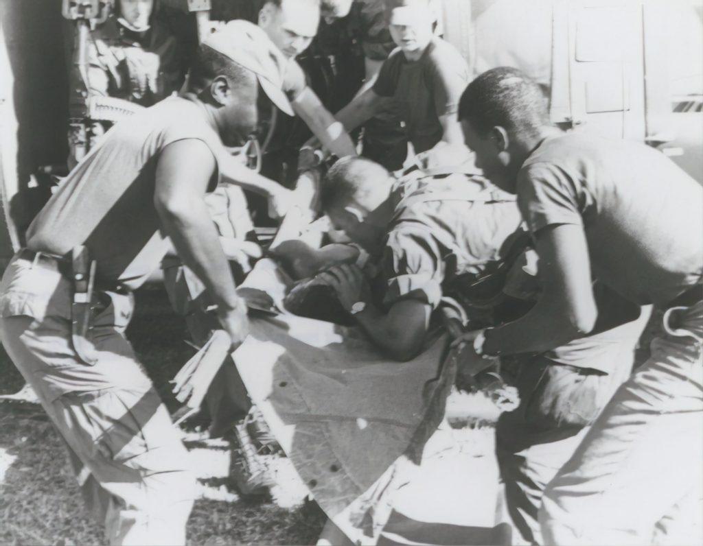 Cinque soldati soccorrono un ferito.